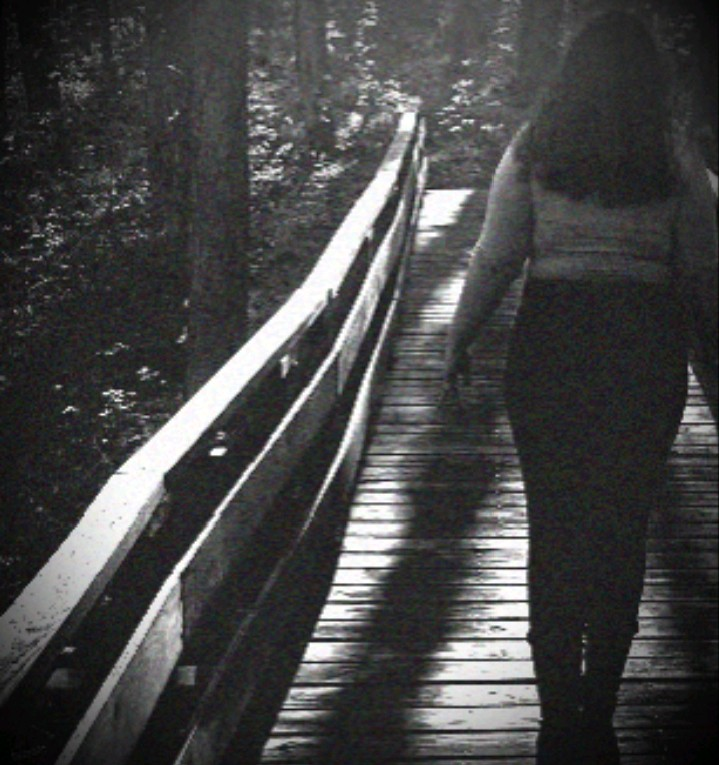 Woman walking away on a bridge to better understand her depression